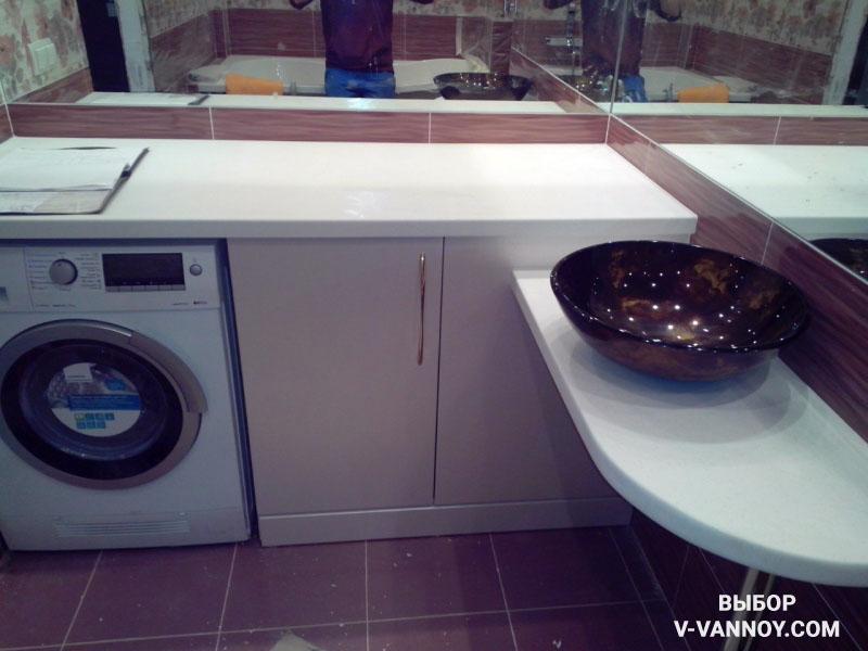 Стиральная машина встроена в мебель для ванны. Такая планировка экономит место.