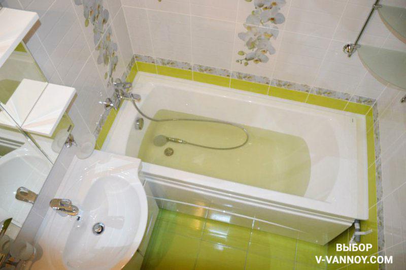 Салатово-белая облицовка с декоративными вставками. Для хранения можно использовать зеркальный шкаф, тумбу под умывальником и подвесной стеклянный уголок.