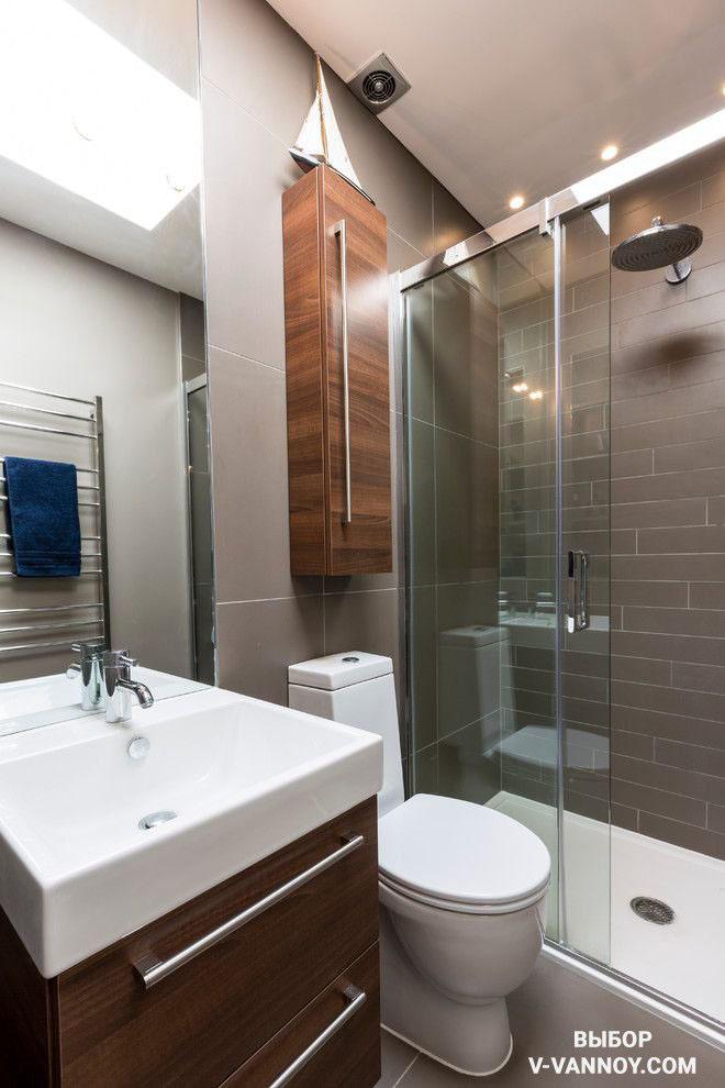 Современный стиль интерьера. Деревянная фактура мебели сочетается с серым цветом кафеля. Материалы облицовки отличаются по формату, но за счет единого тона смотрятся гармонично. Душевая кабина заменяет ванну и занимает минимум места.