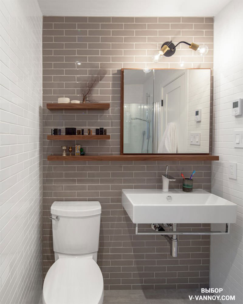 Имитацию кирпичной кладки подчеркивает белая затирка на акцентной стене. Современный стиль формируют отделочные материалы, зеркало-шкаф и полки с древесной текстурой, а также стилизованные «лампочки Ильича».