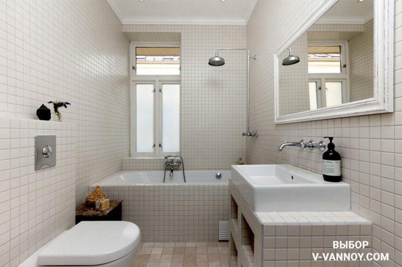 Кремовые стены, пол с текстурой камня и белая сантехника. Квадратные элементы 10х10 см в одном тоне визуально умножают площадь. Свет из окна отражает большое зеркало, добавляя объем.