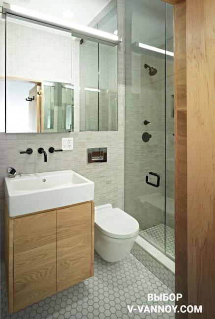 Эко-стиль в интерьере ванной комнаты: деревянная тумба и входная дверь, каменная текстура на стенах, напольное покрытие по форме напоминает соты, а по оттенку – бетон.
