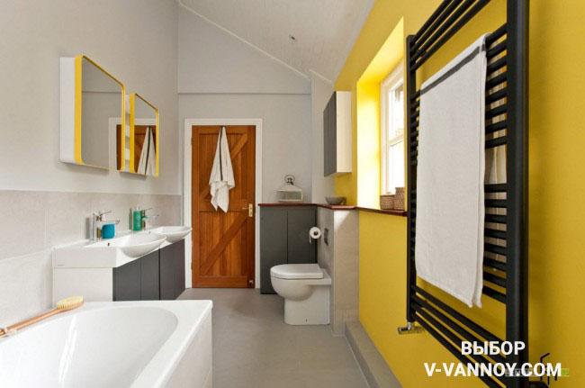 Стена и рамки для зеркал в желтом цвете, а также дверь деревянной фактуры оживляют спокойные оттенки в помещении.