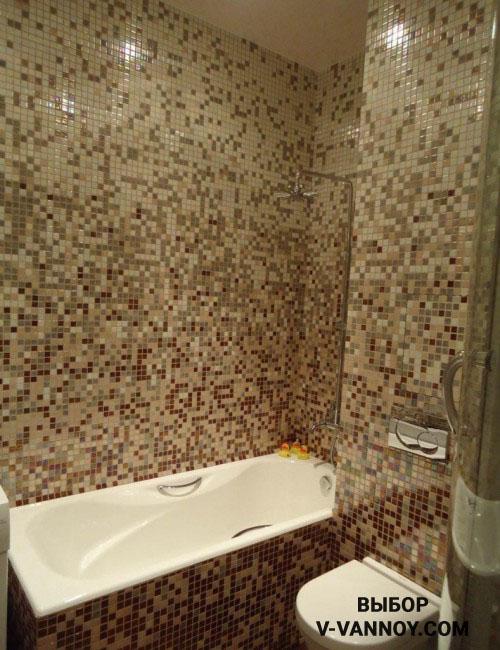 Абстрактная раскладка элементов выглядит стильно и сочетает одновременно четыре оттенка. Специальный экран закрывает ванну и облицован в одном стиле со стенами. За счет подобной отделки площадь воспринимается цельно, несмотря на функциональное зонирование.