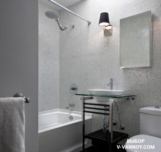 Ракушечник нейтрального оттенка в монохромном интерьере. Перламутровая поверхность стен и зеркало отражают искусственный свет, визуально умножая пространство.