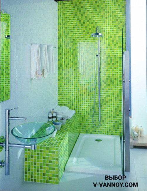 Ярко-салатовая мозаика в оформлении душевой кабины зонирует санузел функционально, а стеклянная перегородка позволяет воспринимать компактную площадь без визуальных преград. Стена напротив зеркала также облицована зеленой мозаикой.