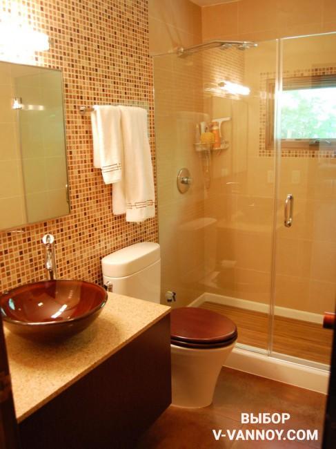 Керамическая мозаика в карамельной гамме. Насыщенно-коричневый присутствует не только на поверхности стен и пола, но и на крышке унитаза, раковине и фасадах тумбы.